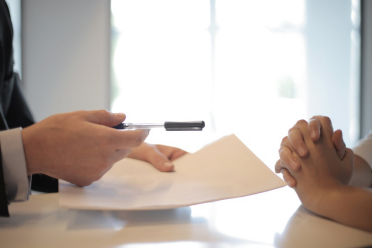 A person giving another person a contract and pen to sign the contract.