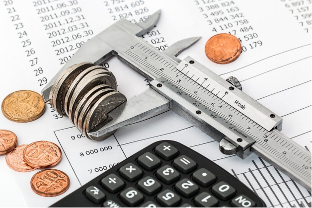 A bank statement, coins, calculator, and vernier calipers.