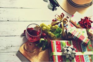 Gifts, wine, and grapes on a wooden board